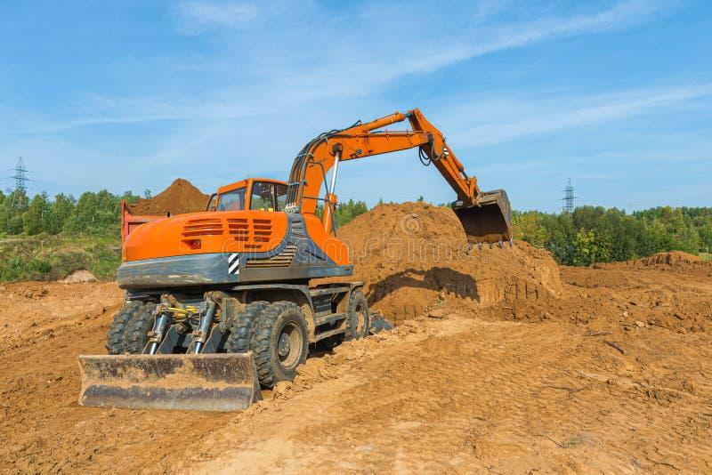 O escavador moderno realiza trabalhos de escavação no local de construção imagens de stock royalty free