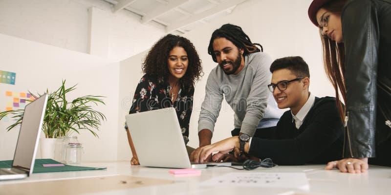O escritório acopla o trabalho junto em equipe em um computador fotos de stock royalty free