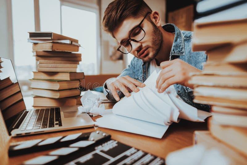 O escritor Working no portátil senta-se com a pilha de livros foto de stock