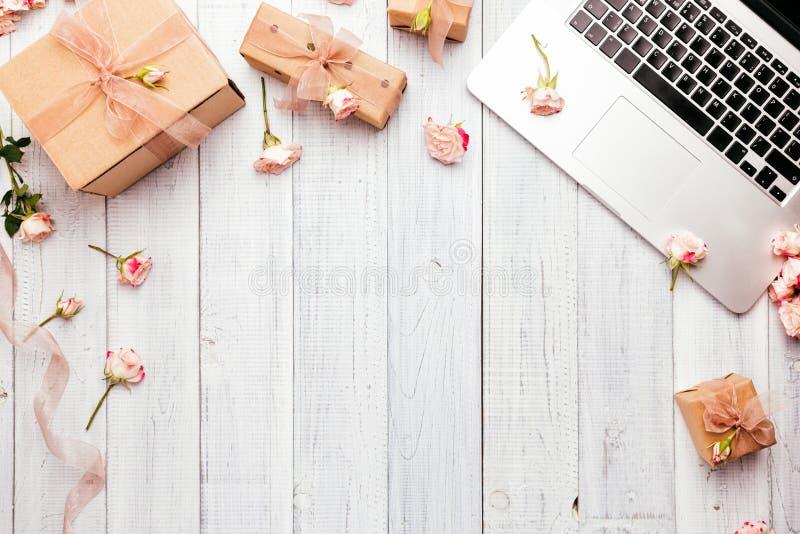O espaço de trabalho com um teclado do portátil, aumentou flores, caixas de presente imagens de stock
