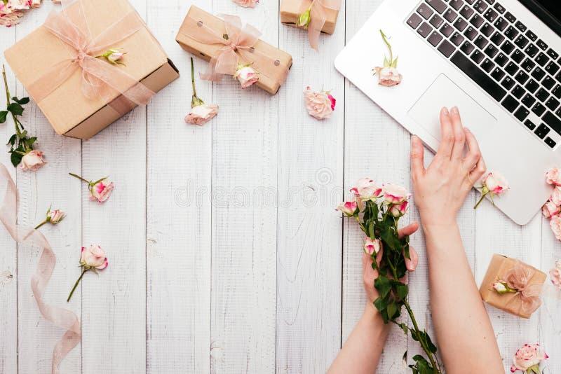 O espaço de trabalho com um teclado do portátil, aumentou flores, caixas de presente imagens de stock royalty free