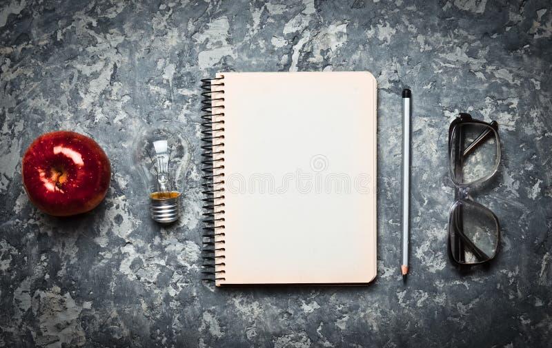 O espaço de trabalho criativo do escritor é inspirador criar Eu tenho uma idéia Bloco de notas, pena, bulbo incandescente, maçã,  fotografia de stock