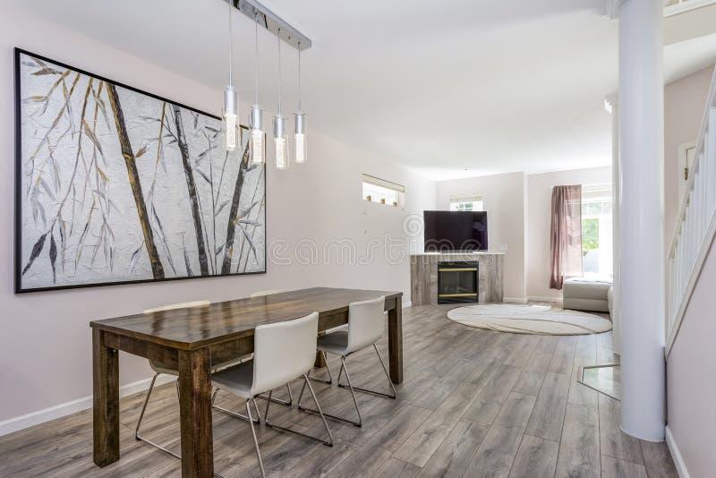 O espaço para refeições moderno com uma tabela de madeira e umas cadeiras de couro fotografia de stock royalty free