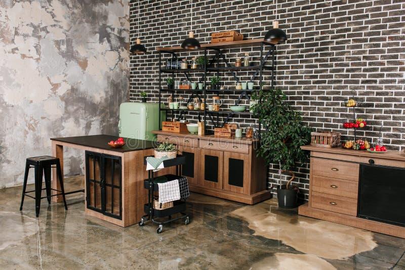 O espaço para refeições no estilo industrial com tabela, cadeiras e refrigerador retro da hortelã Fundo preto da parede de tijolo imagem de stock royalty free