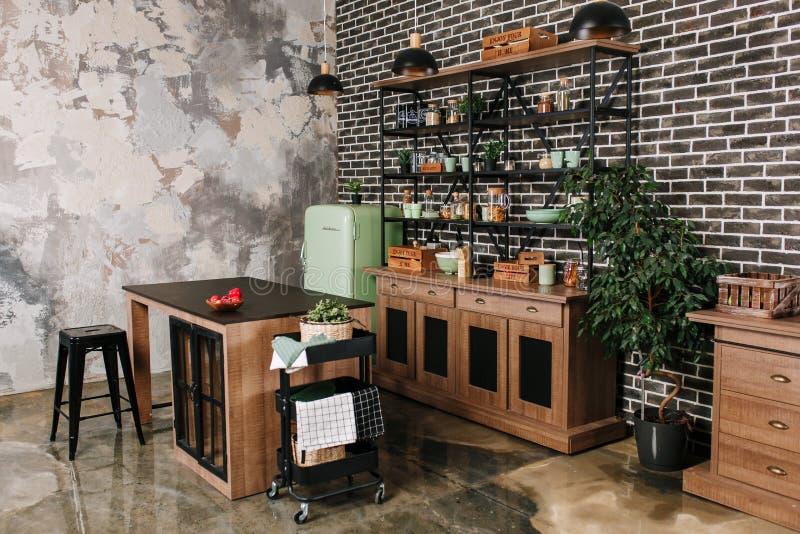 O espaço para refeições no estilo industrial com tabela, cadeiras e refrigerador retro da hortelã Fundo preto da parede de tijolo foto de stock