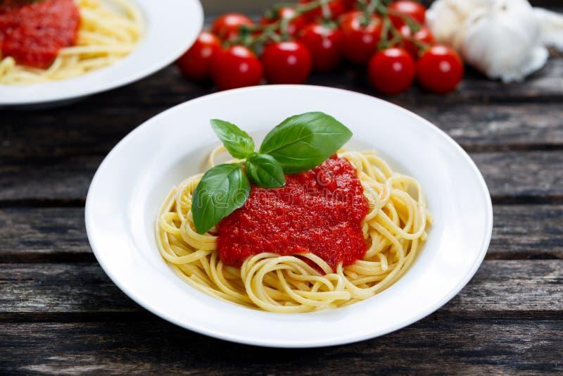 O espaguete com molho e manjericão do marinara sae na parte superior, decorada com os vegetais Na tabela de madeira imagem de stock royalty free
