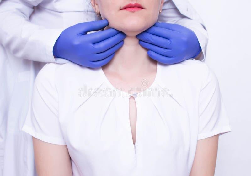 O especialista do doutor diagnostica a palpação na garganta da menina caucasiano para a presença de nós de linfa ampliados e foto de stock royalty free