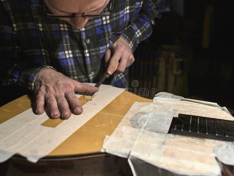 O especialista remove o verniz do corpo da guitarra foto de stock