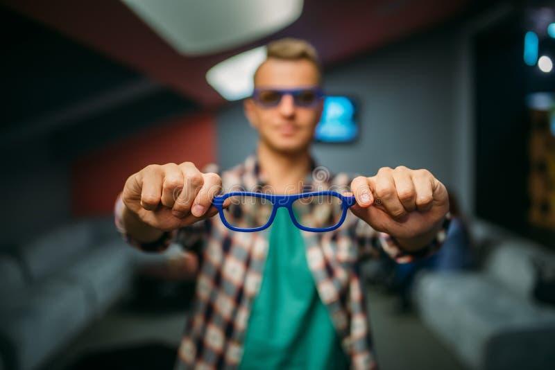 O espectador masculino mostra os vidros 3d no salão do cinema imagem de stock royalty free