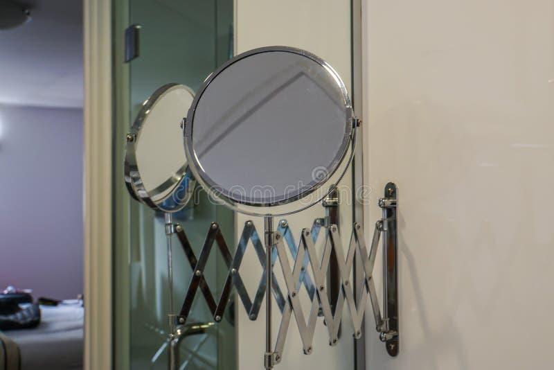 O espelho arredondado para a mulher compõe no banheiro luxuoso imagens de stock