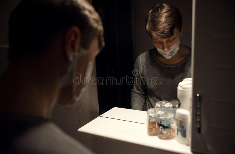 O espelho do homem que barbeia no banheiro imagem de stock