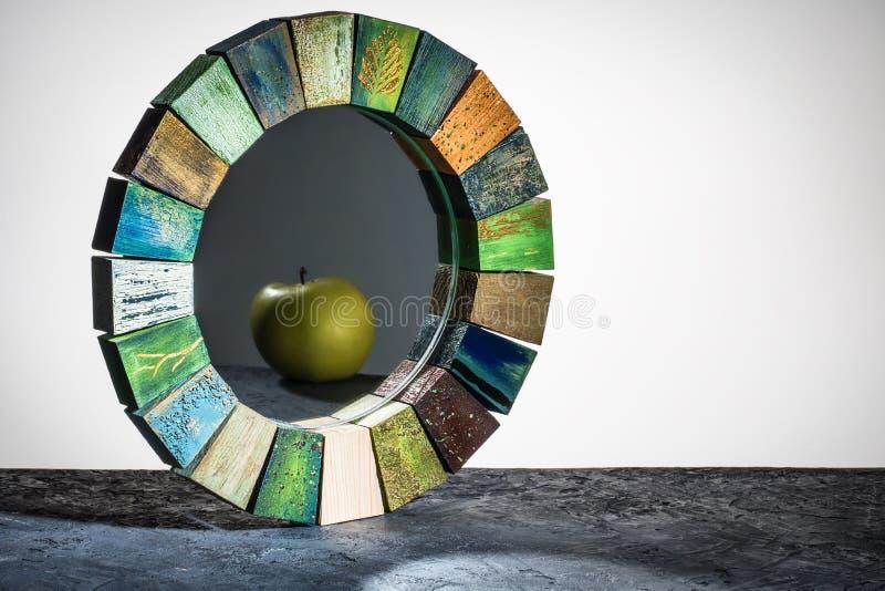 O espelho feito a mão em uma textura tonificada de madeira do quadro rachou a pintura com a maçã do verde da reflexão na tabela fotos de stock