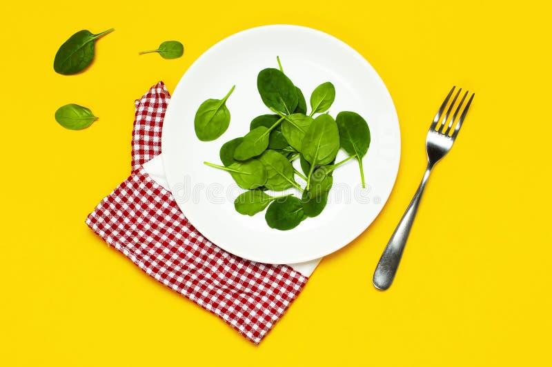 O espinafre verde fresco sae em uma toalha de cozinha branca da forquilha da placa no espaço colocado da cópia da opinião superio foto de stock