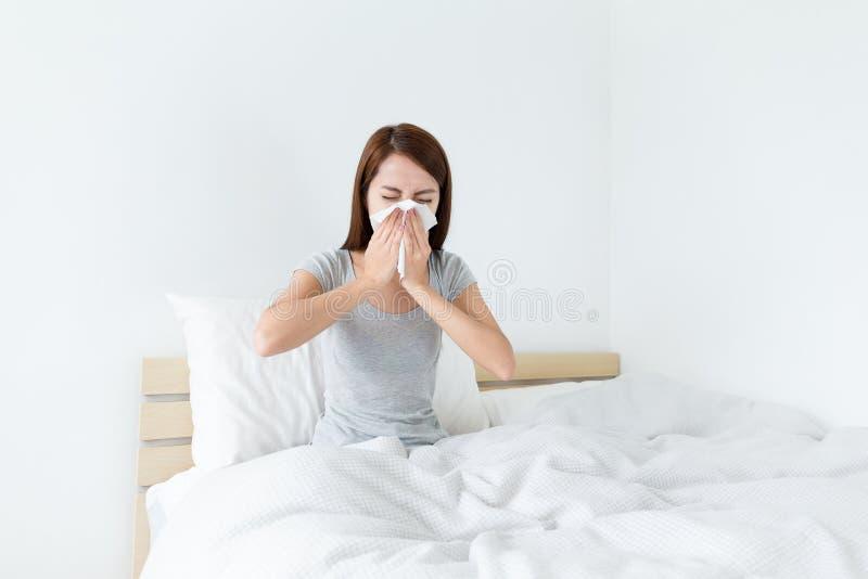O espirro da jovem senhora na cama e precisa mais resto foto de stock royalty free