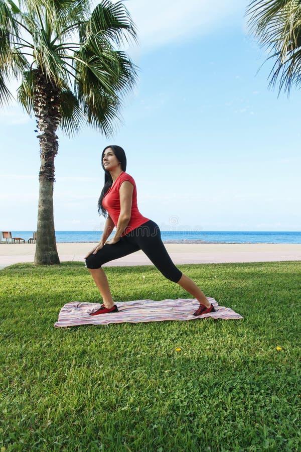 O esporte do exercício da mulher exercita a ocupa fora na praia imagem de stock