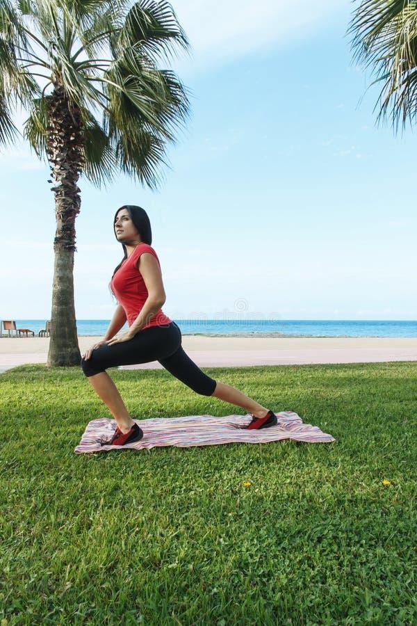 O esporte do exercício da mulher exercita a ocupa fora na praia fotos de stock royalty free