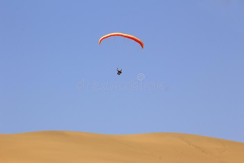 O esporte do salto da duna de areia e de executar manobras acrobáticas no ar durante a queda livre antes de aterrar pelo paraqued imagens de stock royalty free