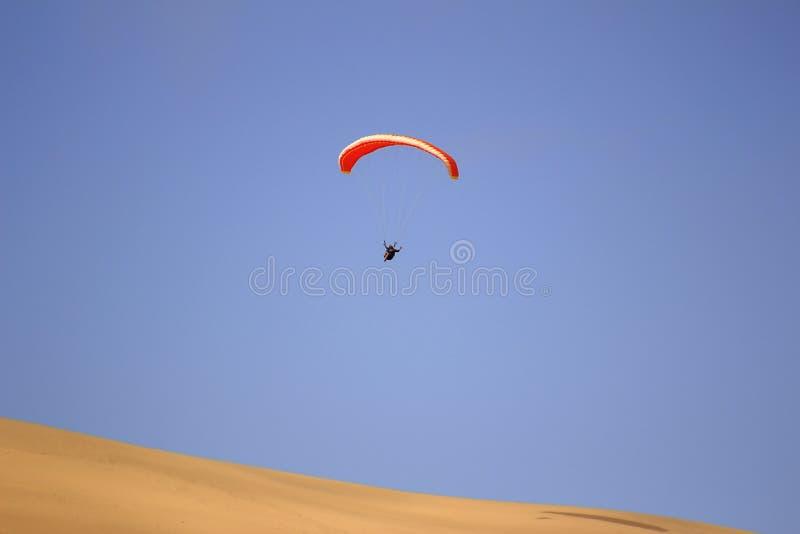 O esporte do salto da duna de areia e de executar manobras acrob?ticas no ar durante a queda livre antes de aterrar pelo paraqued fotografia de stock