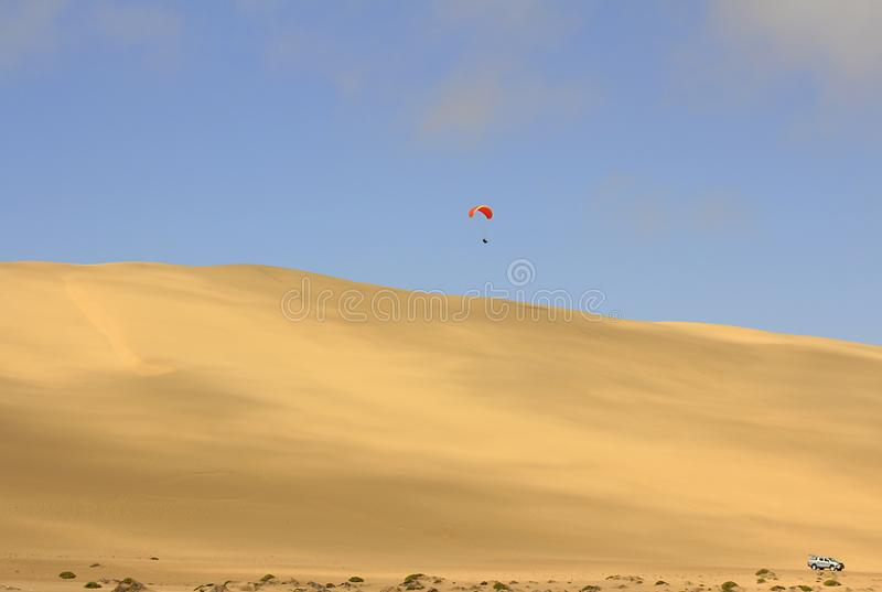 O esporte do salto da duna de areia e de executar manobras acrob?ticas no ar durante a queda livre antes de aterrar pelo paraqued imagens de stock royalty free