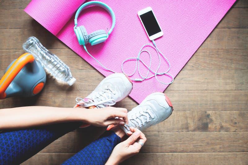 O esporte e a mulher saudável que amarram suas sapatas, malham em casa, Wellbe fotografia de stock
