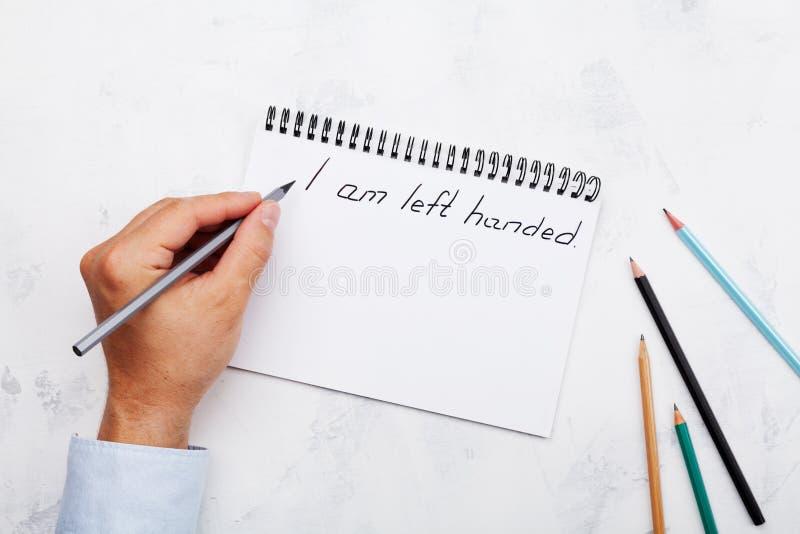 O esquerdista escreve no caderno na tabela branca de cima de Dia internacional dos Lefthanders fotografia de stock