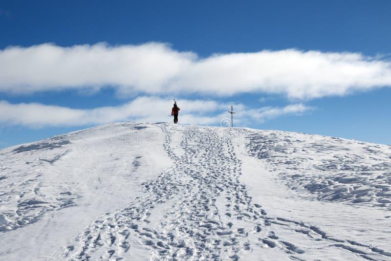 O esquiador com os esquis em seu ombro vai acima à parte superior da montanha imagens de stock royalty free