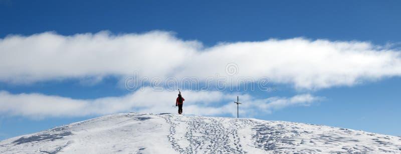 O esquiador com os esquis em seu ombro vai acima à parte superior da montanha fotografia de stock royalty free