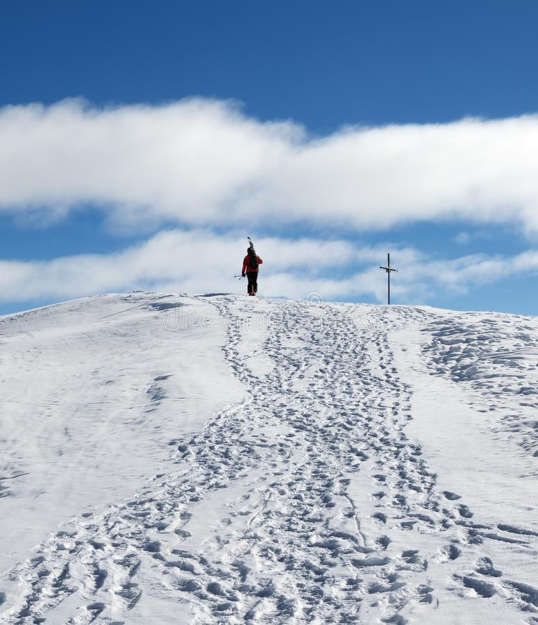 O esquiador com os esquis em seu ombro vai acima à parte superior da montanha nevado imagens de stock
