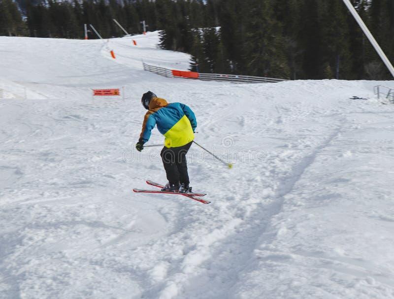 O esquiador da criança executa um salto alto com o esqui em Chopok, Eslováquia Estação do inverno, revestimento colorido Menino p imagem de stock