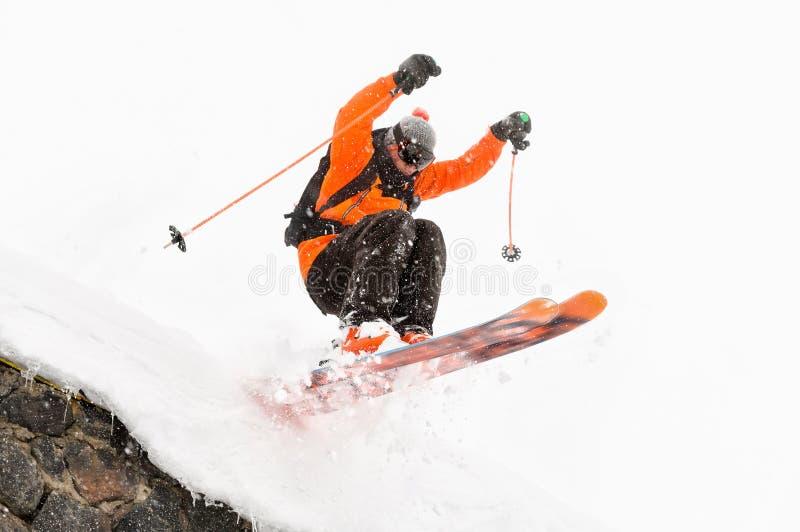 O esquiador do atleta em um fundo claro com um salto move-se fora do telhado de uma cabana coberto de neve com os flocos do voo d fotografia de stock