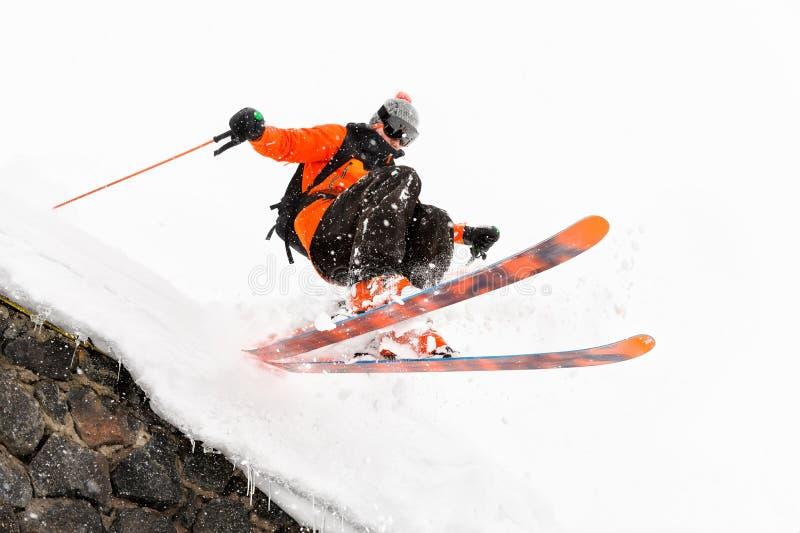O esquiador do atleta em um fundo claro com um salto move-se fora do telhado de uma cabana coberto de neve com os flocos do voo d imagem de stock royalty free