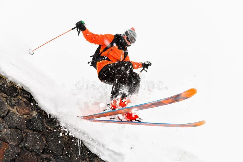 O esquiador do atleta em um fundo claro com um salto move-se fora do telhado de uma cabana coberto de neve com os flocos do voo d imagens de stock royalty free