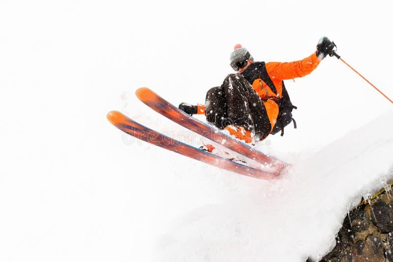 O esquiador do atleta em um fundo claro com um salto move-se fora do telhado de uma cabana coberto de neve com os flocos do voo d fotografia de stock royalty free