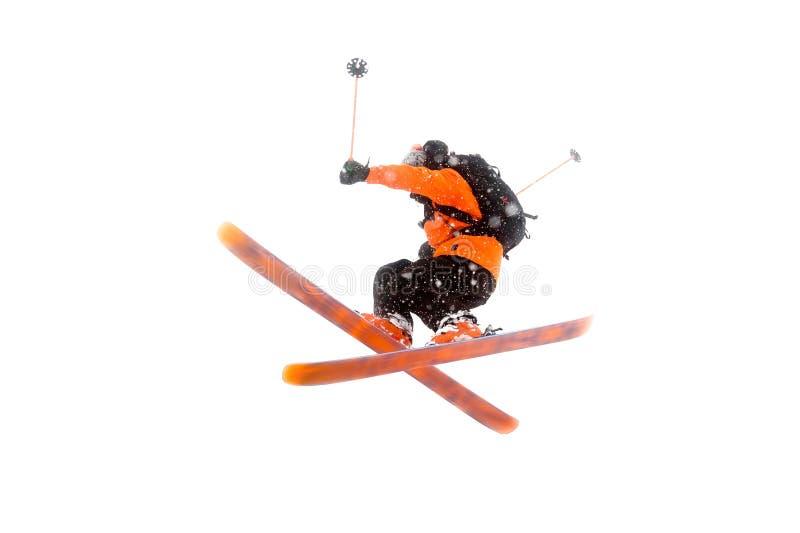 O esquiador do atleta no terno preto alaranjado faz o truque do salto cruzando os esquis foto real feita nas montanhas fotos de stock