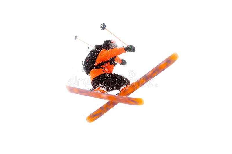 O esquiador do atleta no terno preto alaranjado faz o truque do salto cruzando os esquis foto real feita nas montanhas foto de stock