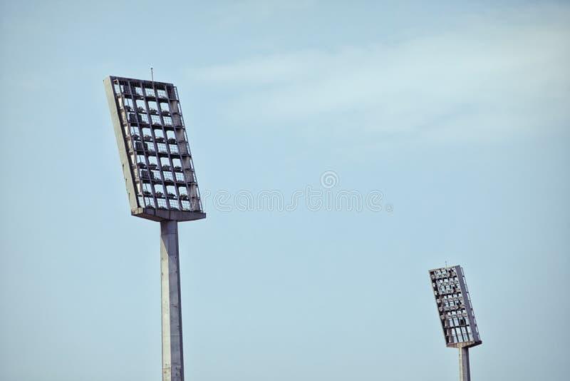 O estádio de futebol ilumina refletores contra um céu azul vazio fotografia de stock