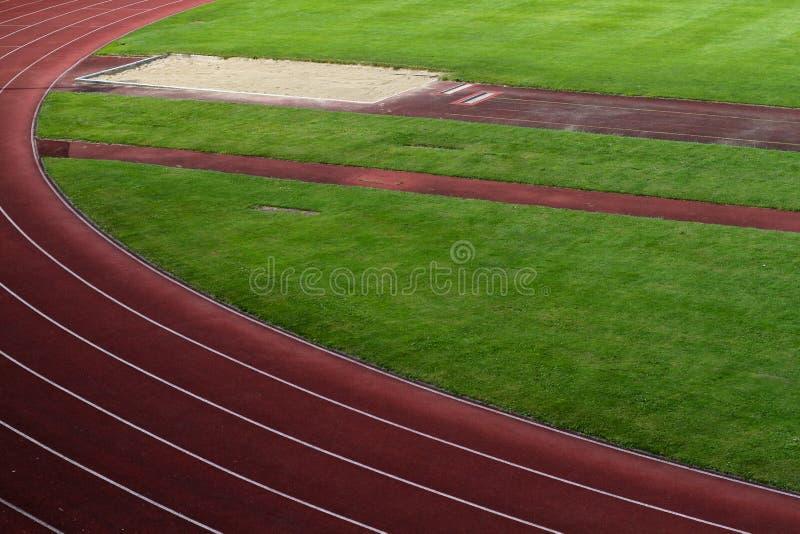 O estádio dos esportes com trilhas de raça e o salto longo pit imagens de stock