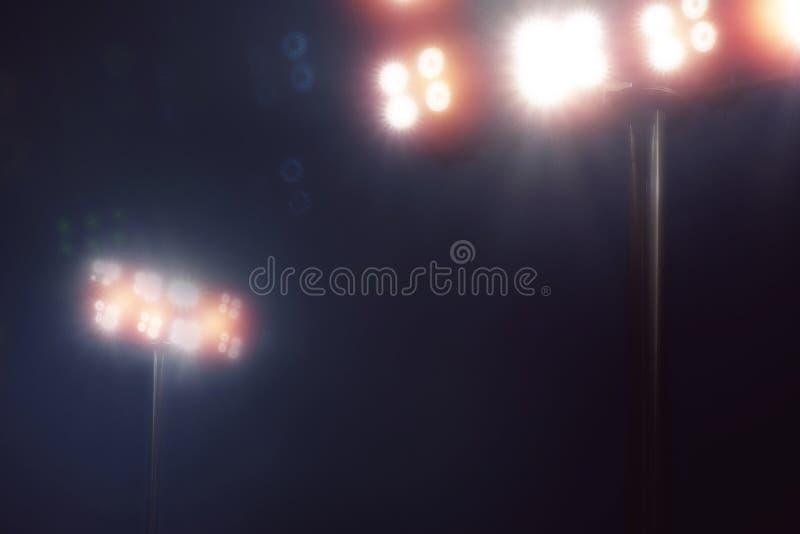 O estádio ilumina-se no jogo do esporte no céu noturno escuro foto de stock royalty free