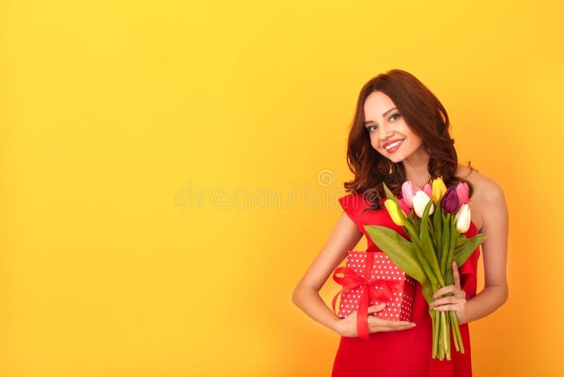 O estúdio da jovem mulher isolado no amarelo em um vestido vermelho apresenta imagem de stock