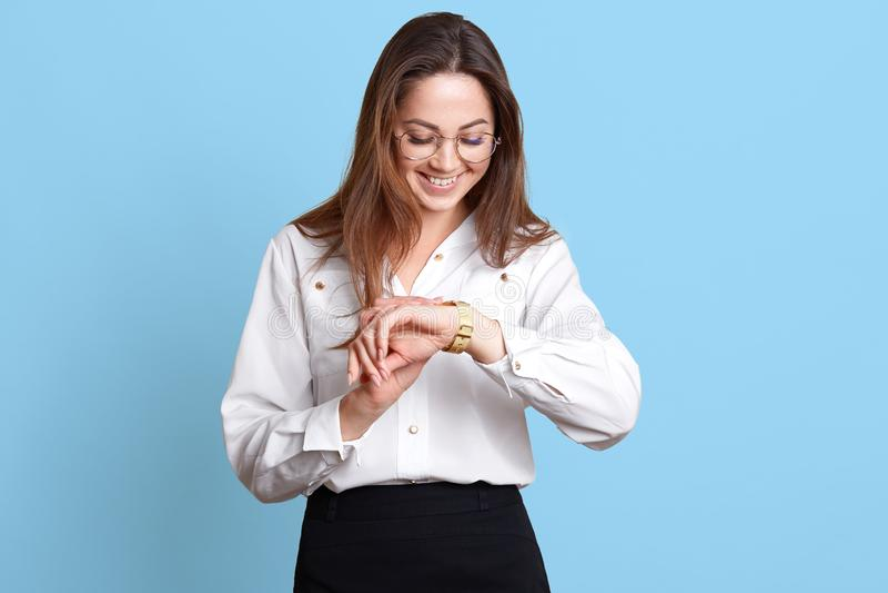 O estúdio disparado da jovem mulher moreno bonita de sorriso feliz na roupa formal que está e que verifica o tempo, estando na pr imagens de stock