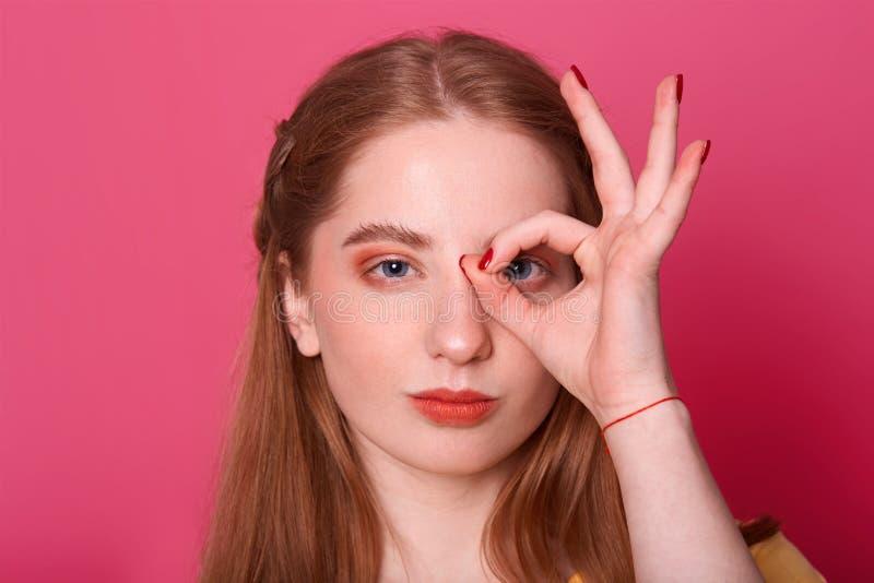 O estúdio disparado da jovem mulher séria atrativa, faz o sinal da aprovação, cobre seu olho, expressa a confiança, modelo levant imagem de stock