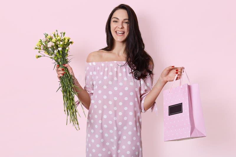 O estúdio disparado da mulher europeia nova de sorriso tem o cabelo ondulado longo escuro, vestido vestindo da rosa do às bolinha imagens de stock