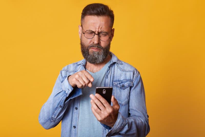 O estúdio disparado do homem envelhecido médio com apelo da aparência, barba escura do hairand, vestida ocasionalmente usa o smar fotos de stock