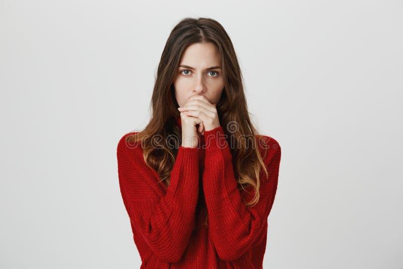 O estúdio disparou da fêmea nova pensativa séria com cabelo longo na boca de fechamento da camiseta vermelha, concentrando-se con fotos de stock