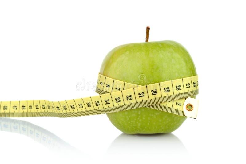 O estúdio disparou da maçã saudável verde inteira com fita métrica imagem de stock