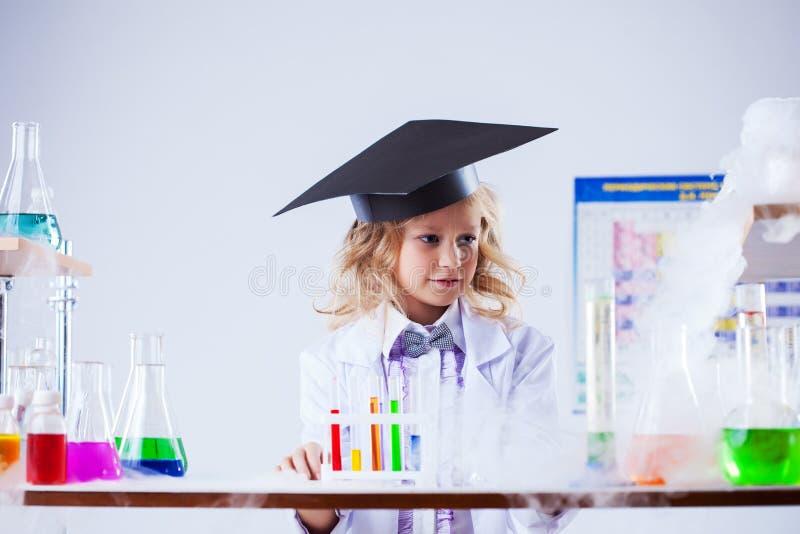 O estúdio disparou da menina séria que levanta no laboratório químico fotos de stock