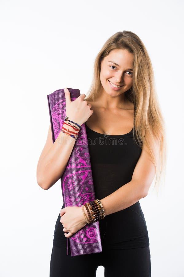 O estúdio disparou da mulher loura bonita nova que guardam a esteira da ioga e do levantamento pronto para o gym imagens de stock royalty free