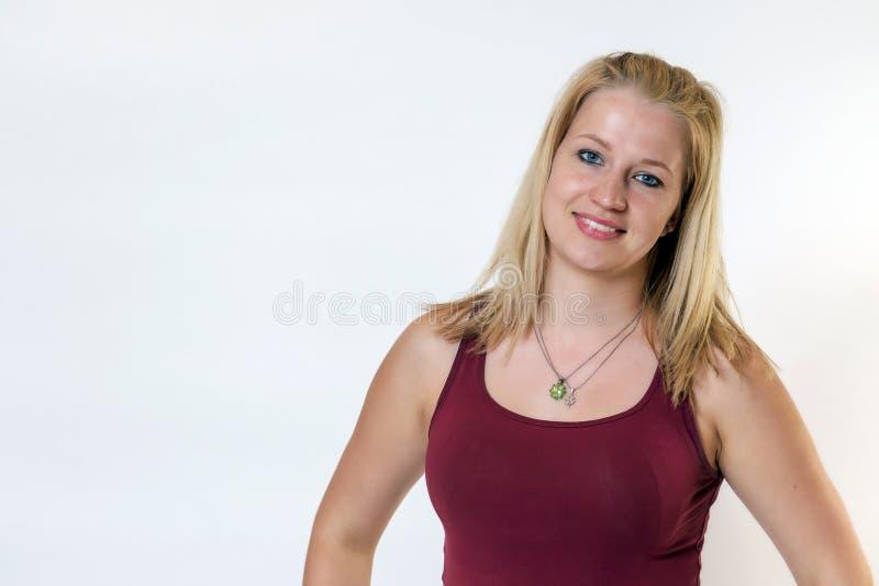 O estúdio disparou da mulher loura nova que sorri na câmera fotos de stock royalty free