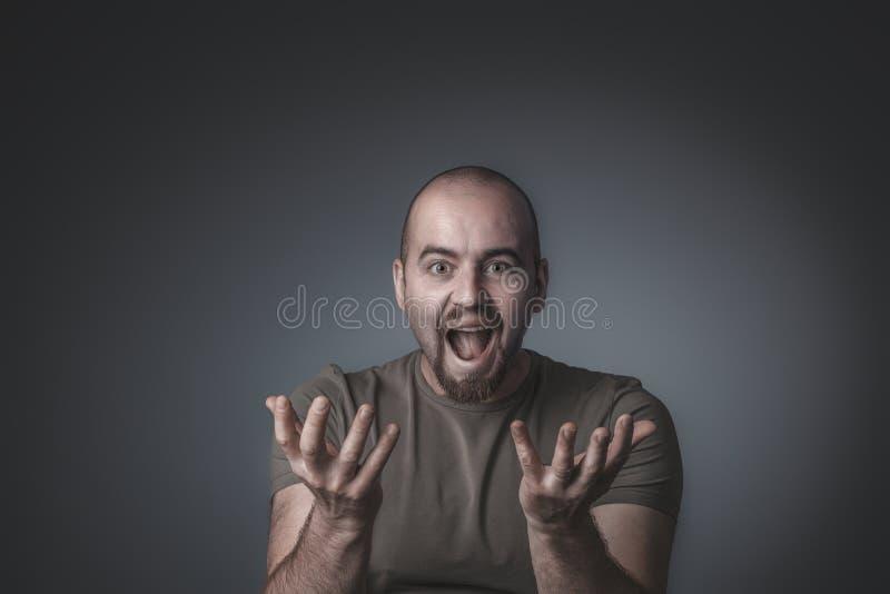 O estúdio disparou de um homem com uma expressão surpreendida e entusiástica fotos de stock