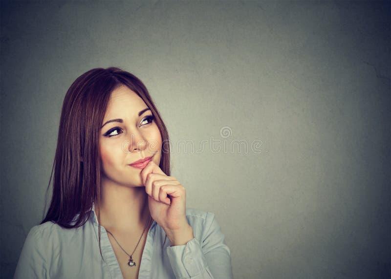 O estúdio disparou de uma jovem mulher bonita que olha pensativa fotos de stock